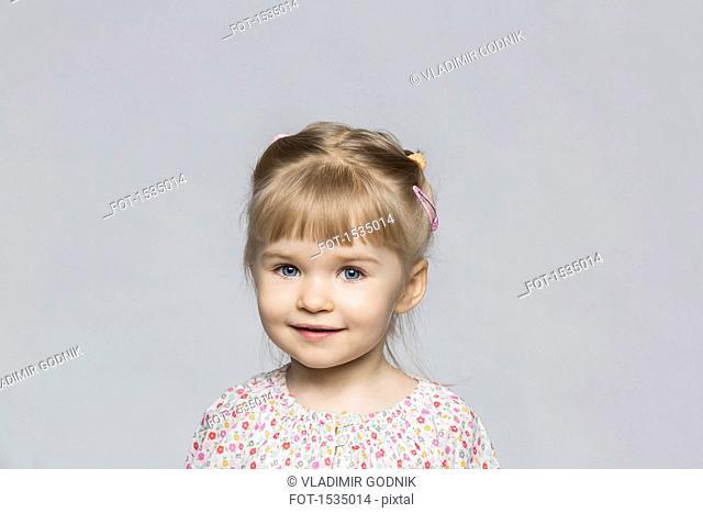 Portrait of smiling girl against gray background