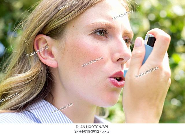 MODEL RELEASED. Young woman using inhaler