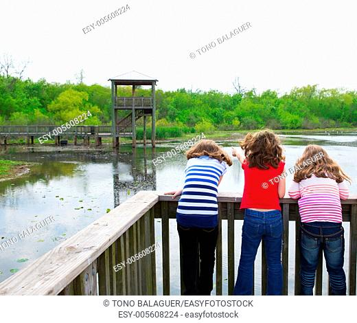 kid children girls looking and pointing at park lake in Texas rear view