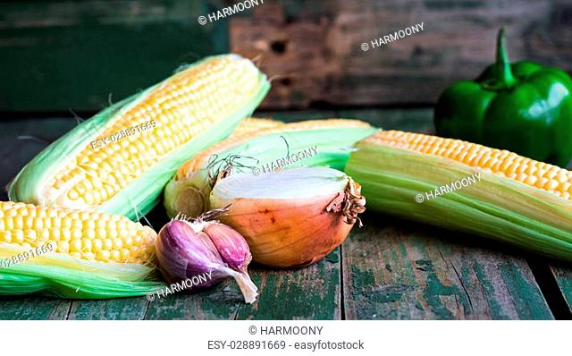 raw corn on the cob on a green wooden background, vegetables, horizontally