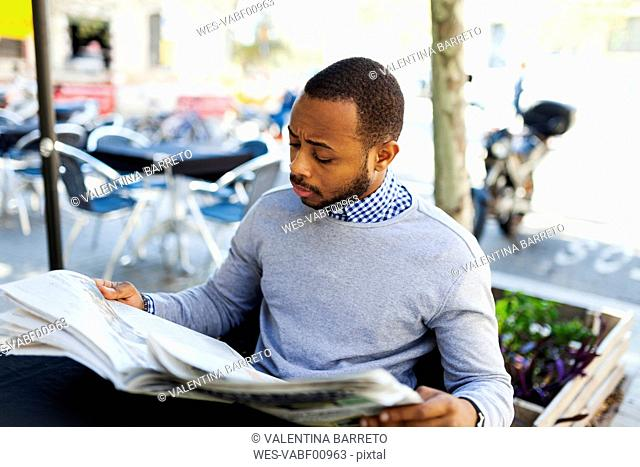 Young man reading newspaper at street cafe
