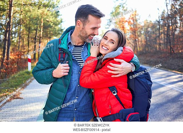 Happy couple embracing on a road in the woods during backpacking trip