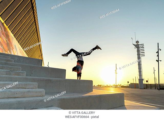 Acrobat doing handstand on stairs at sunrise