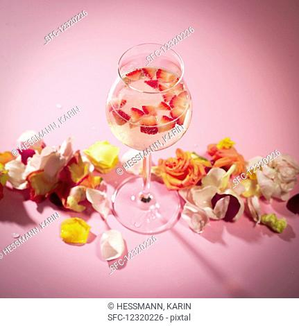 A glass of rose punch with chopped strawberry in front of a pink background
