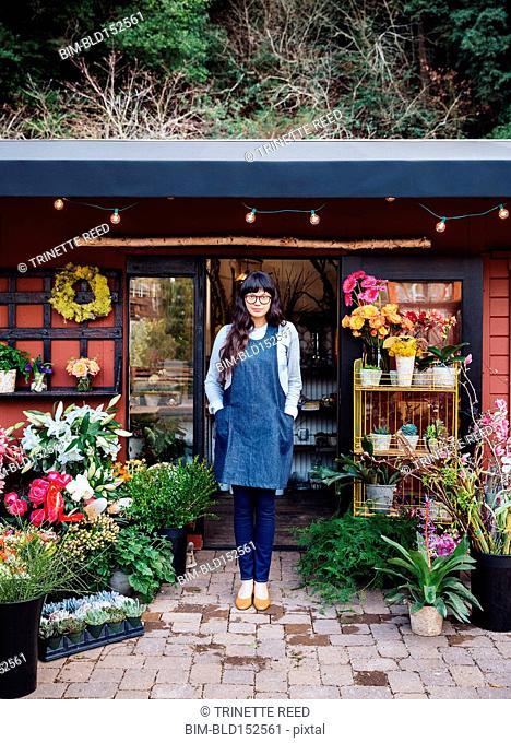 Mixed race florist standing outside shop