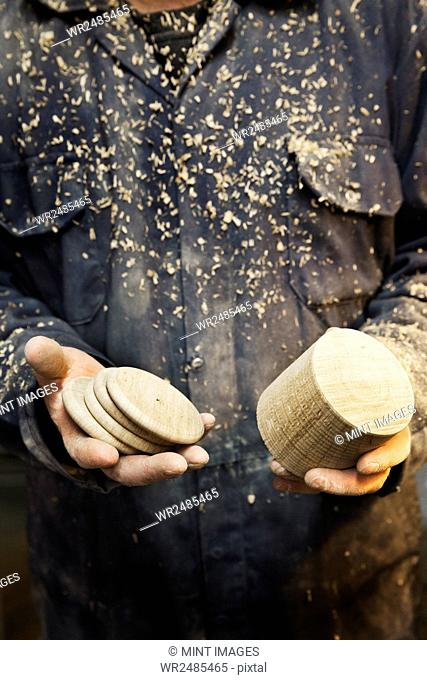 Close up of a man in overalls covered in sawdust, holding a wooden turned shape and wooden discs in his hands