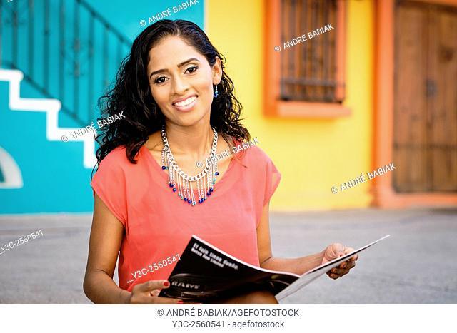 Attractive hispanic woman with jewelry sitting at a sidewalk reading magazine