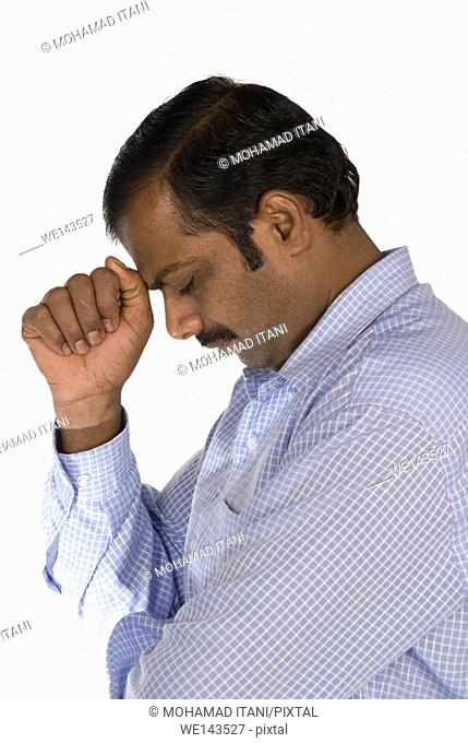 side view of a sad Indian man