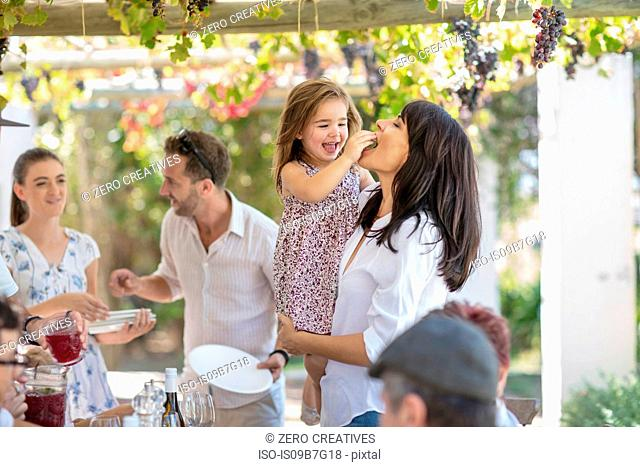 Girl feeding mother at outdoor family lunch
