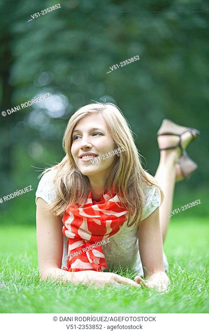 Pretty blonde woman amiling lying down in park