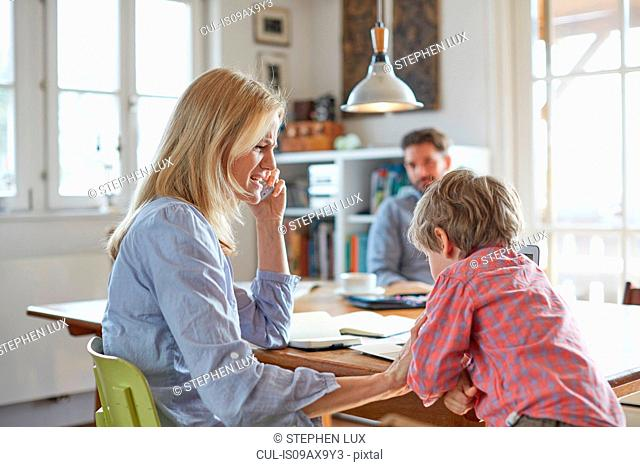 Parents and son working in home office