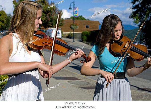 Two girls play their violins at 'Music on the landing' in Gibsons, on the Sunshine Coast, Vancouver coast and mountain region, British Columbia, Canada