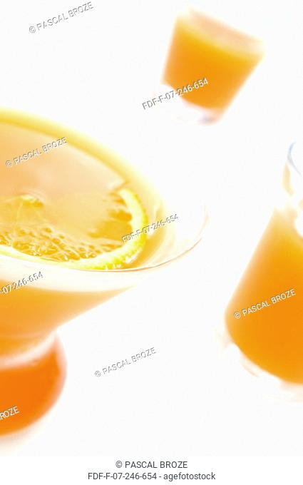 Close-up of a glass of orange juice with a slice of an orange