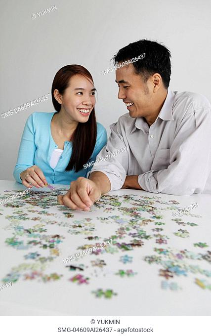 Young couple working on puzzle together
