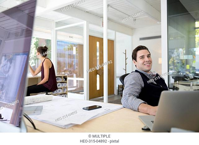 Portrait smiling businessman working at laptop in office