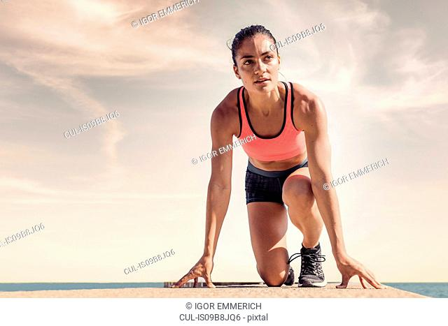 Young woman on sea wall, in start position, preparing for run