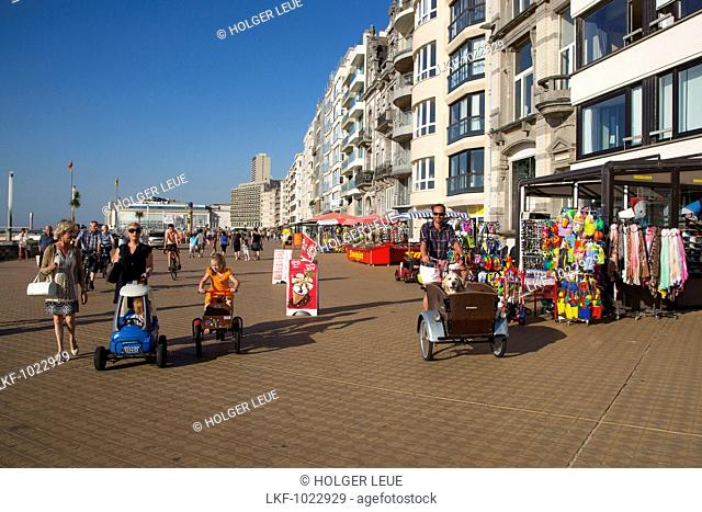 Man on bicycle with cart and Golden Retriever dog in it on the beach promenade, Ostend, Flanders, Flemish Region, Belgium