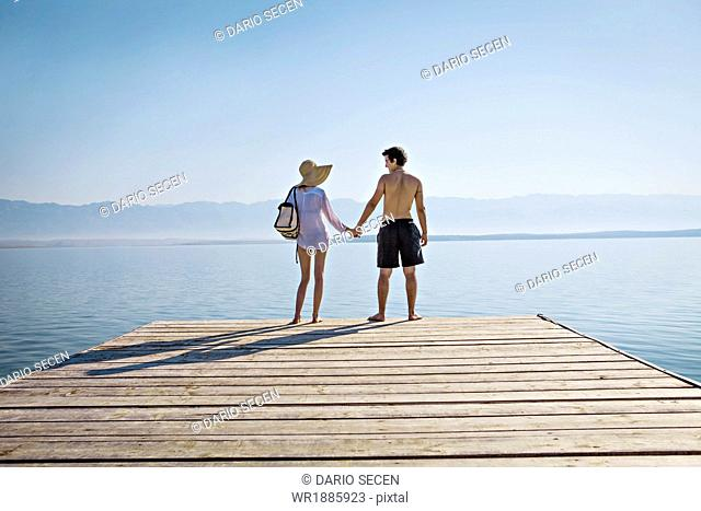 Croatia, Young couple on boardwalk holding hands, by the sea