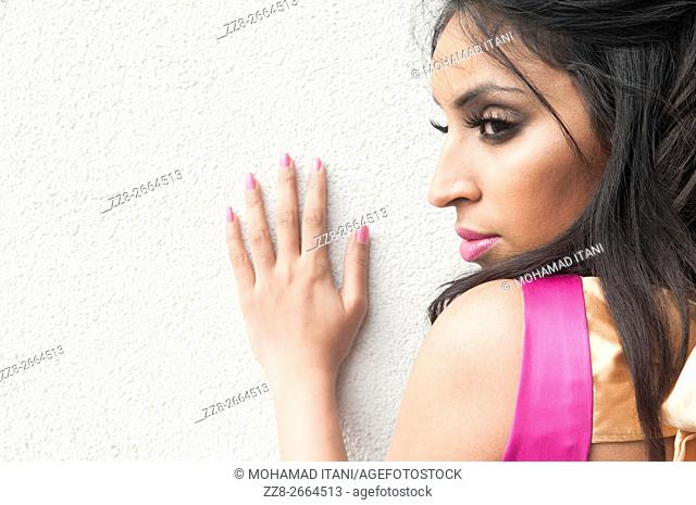 Serious Indian woman hnd pushing against the wall looking away