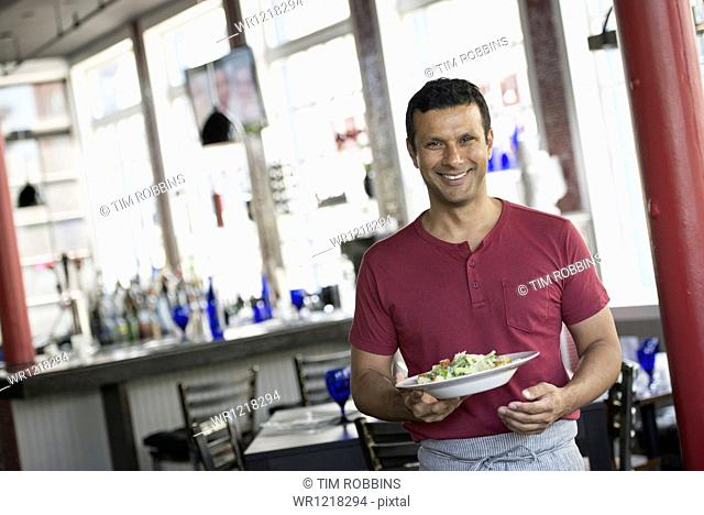 A cafe interior. A man in a waiter's apron serving a meal