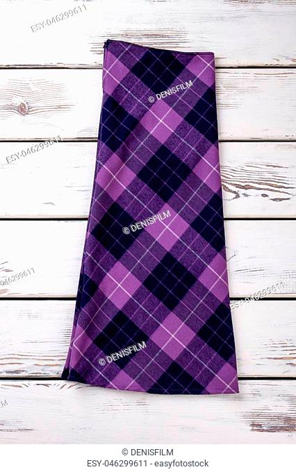 Folded woolen purple checkered skirt. Wooden desks surface background. Cropped vertical image
