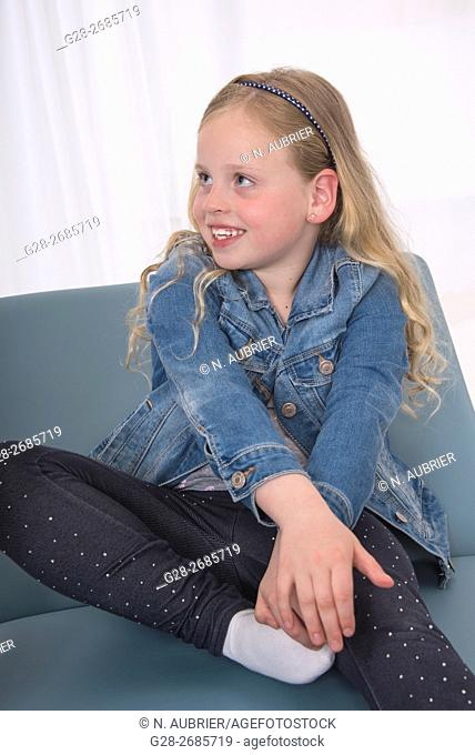 Happy smiling 6 year old girl, with long blond hair, sitting on a sofa at home