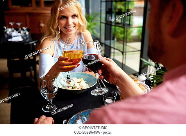 Over shoulder view of couple raising a toast at restaurant table