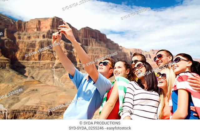 group of happy friends taking selfie by cell phone