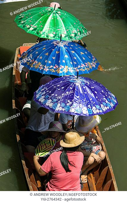 Tourists with coloured parasols floating market Damnoen Saduak outside Bangkok Thailand