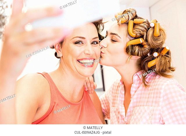 Two female friends, foam rollers in hair, taking selfie with smartphone