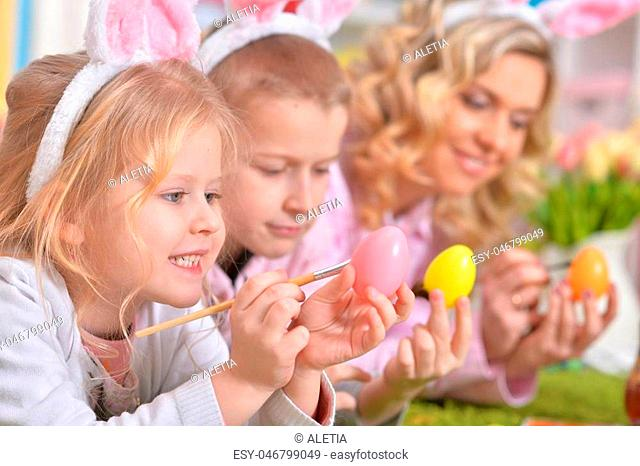 Happy family with rabbit ears preparing for Easter and color eggs