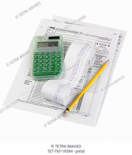 Still life of tax forms, pencil, calculator