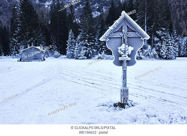 Europe, Italy, Veneto, Belluno. A wooden hut and a crucifix covered with ice in Ansiei valley in winter, Auronzo di Cadore, Dolomites