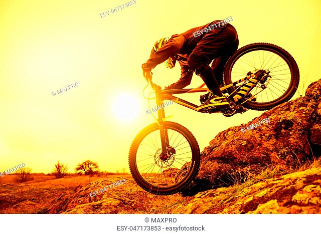 Professional Cyclist Riding Mountain Bike Down the Rocky Hill. Extreme Sport and Enduro Biking Concept