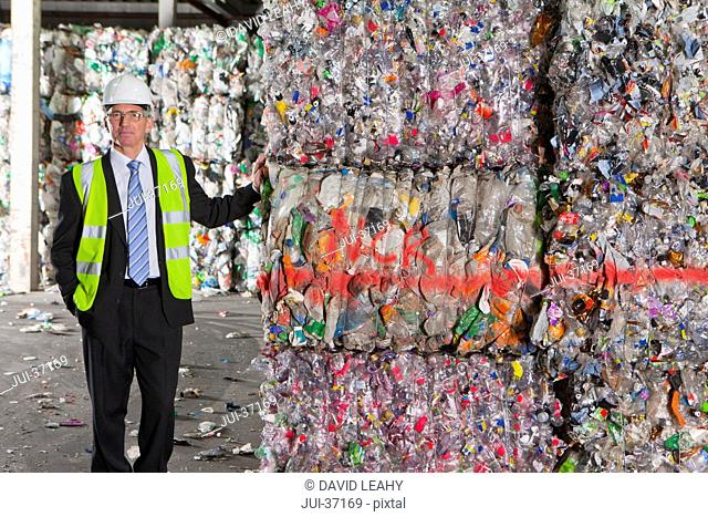 Portrait of confident businessman leaning on bales of recycled plastic in recycling plant