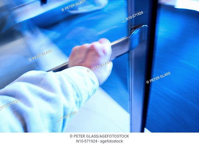 Close-up of a man's hand as he walks through a revolving door