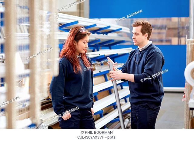Manger mentoring young female worker in roller blind factory