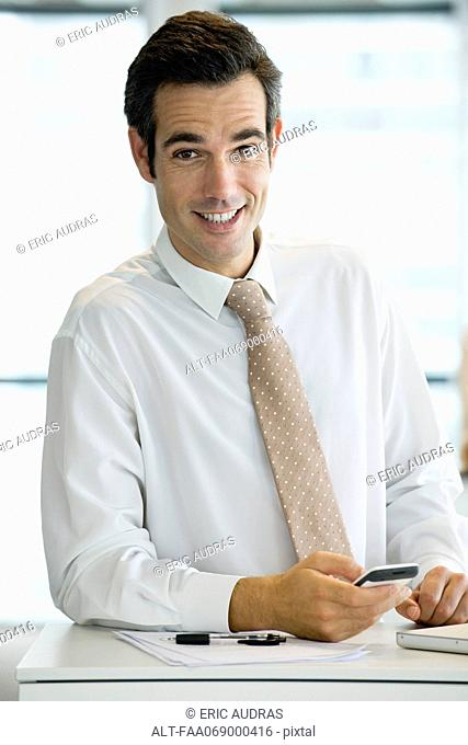 Businessman holding cell phone, portrait