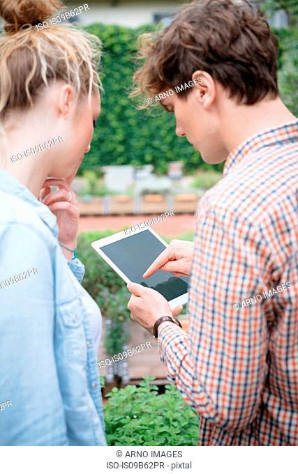Couple in garden using digital tablet