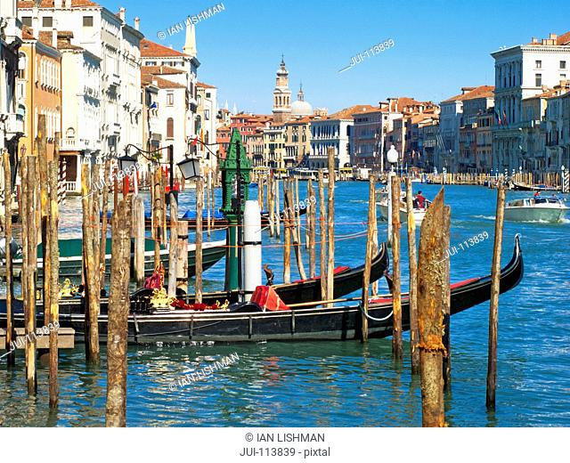 Gondolas moored in sunny canal in front of architectural buildings in Venice, Italy
