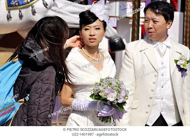 Hong Kong: newlyweds getting ready to pose for the photographer in Tsim Sha Tsui