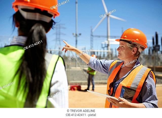 Female engineer with digital tablet talking to colleague at wind turbine power plant