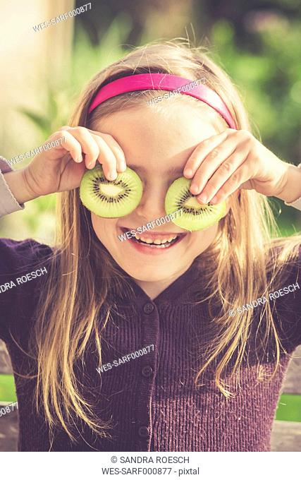 Smiling girl covering eyes with slices of kiwi