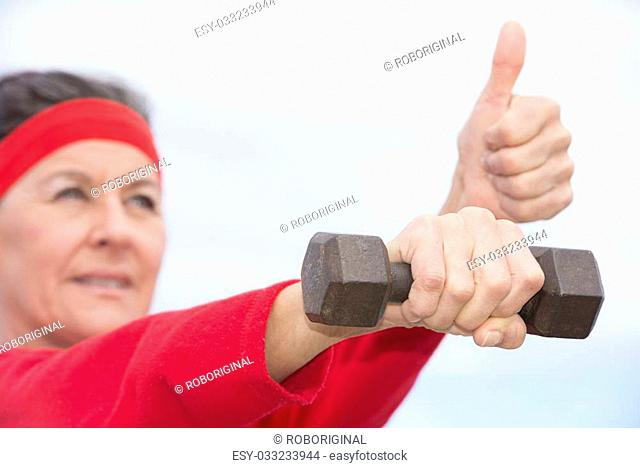 Portrait beautiful mature woman showing active retirement, excercising with weights arms up outdoor, positive, confident, thumbs up, smiling