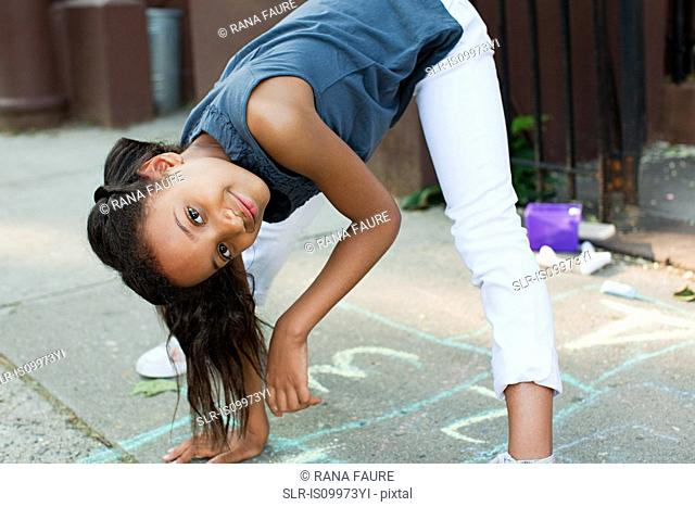 Girl playing on sidewalk, smiling