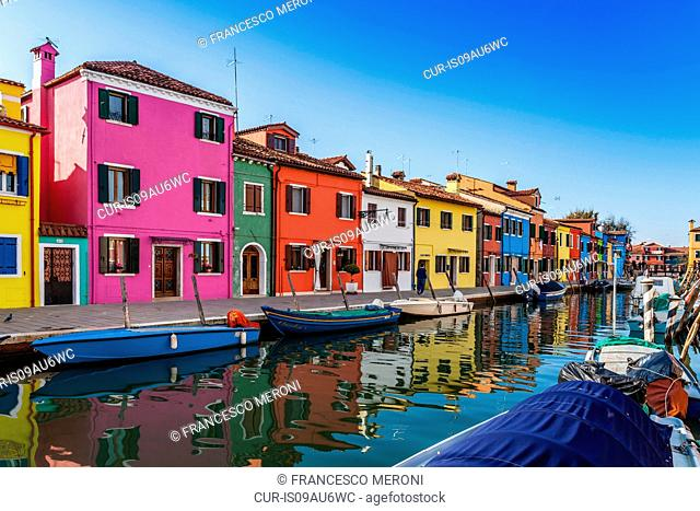 Multi-colored houses and boats on canal waterfront, Burano, Italy