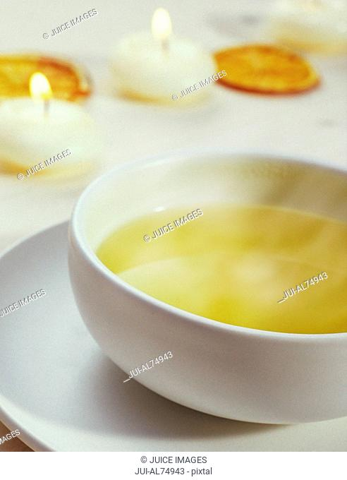 Detail view of a mug of tea with dried orange slices and tea candles on a hardwood surface