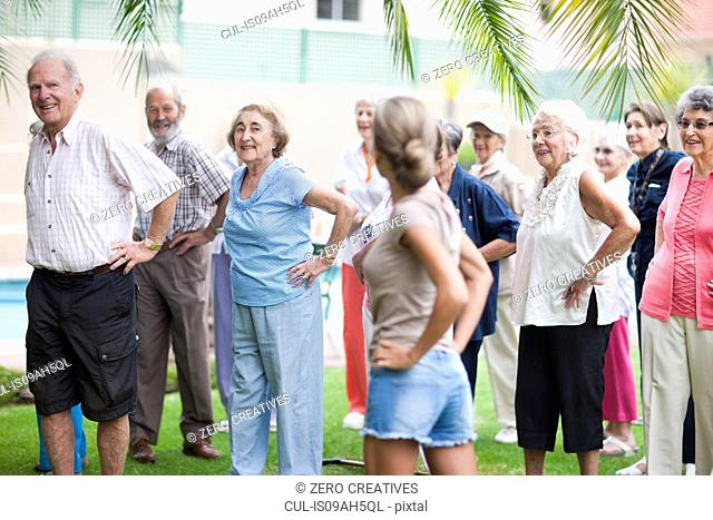 Large group of seniors exercising in retirement villa garden