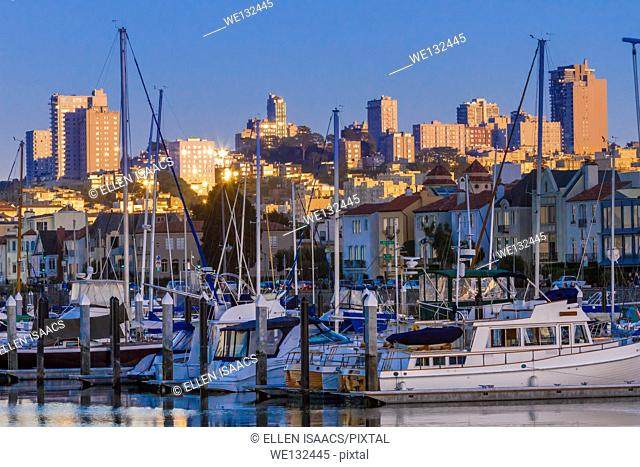 Boats docked in harbor in front of marina district houses and San Francisco skyline at twilight