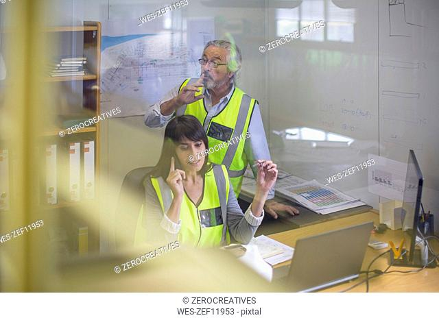 Female construction engineer making a call in site office